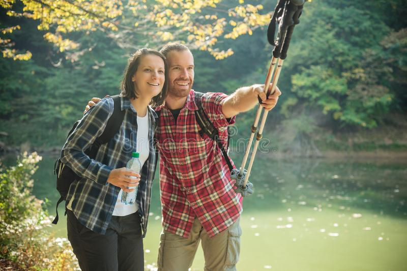 Pares novos felizes de sorriso que caminham ao longo da costa do lago, abraçando-se imagem de stock