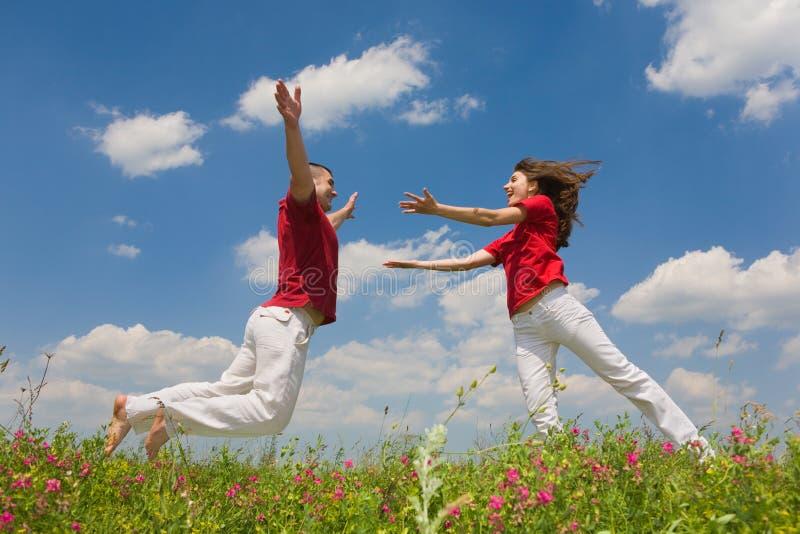 Pares novos felizes do amor que saltam sob o céu azul imagens de stock royalty free