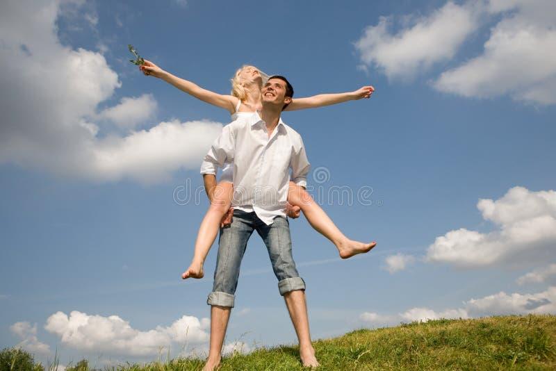 Pares novos felizes do amor - saltando sob o céu imagem de stock royalty free