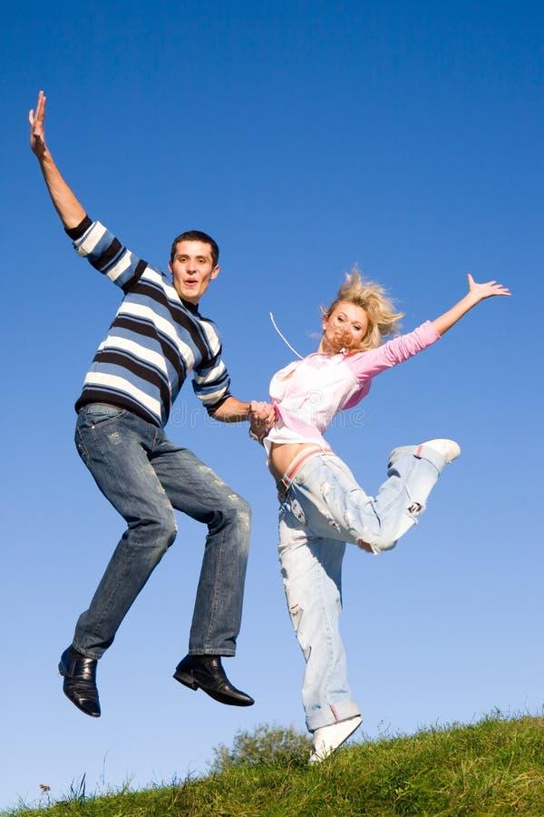 Pares novos felizes do amor - saltando sob o céu azul foto de stock royalty free