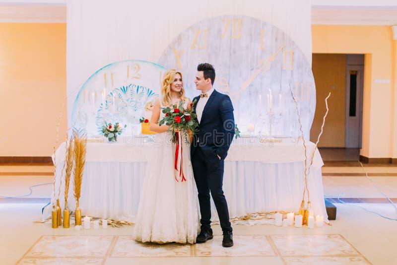 Pares novos felizes do casamento que levantam com o ramalhete das rosas no restaurante imagens de stock