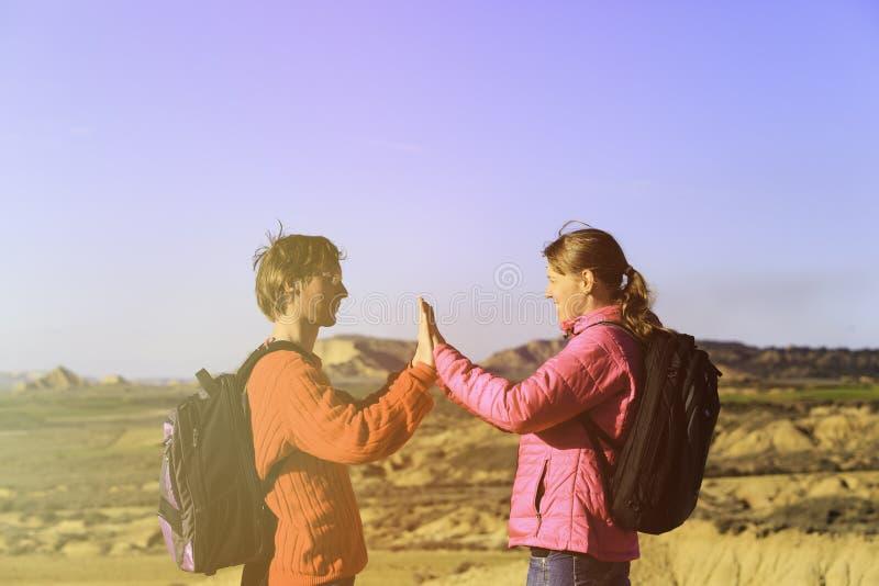 Pares novos felizes do turista que caminham nas montanhas fotografia de stock royalty free