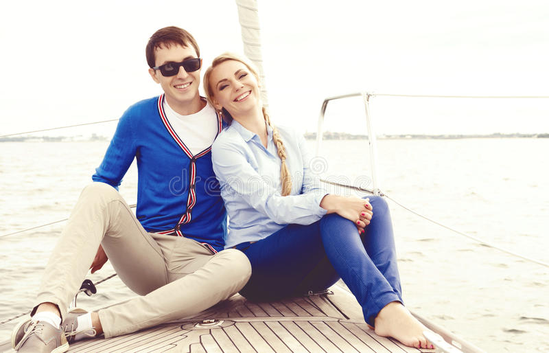 Pares novos felizes e bonitos que sentam-se na plataforma e que têm ir fotografia de stock royalty free