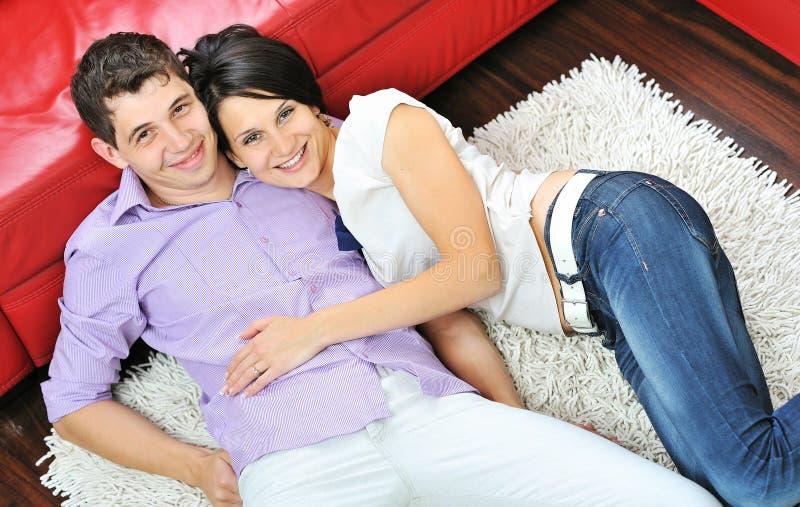 Pares novos felizes em casa fotografia de stock royalty free