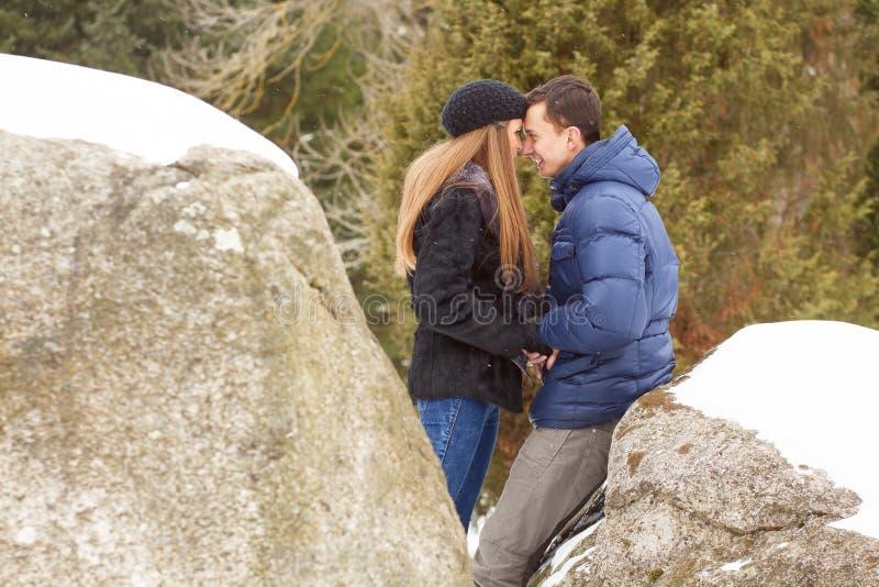 Pares novos felizes em montanhas do inverno imagem de stock royalty free