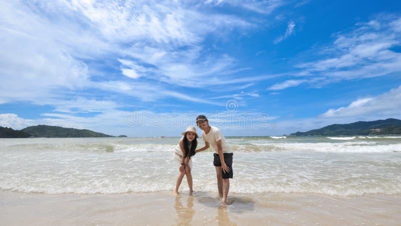 Pares novos felizes em uma praia tropical foto de stock