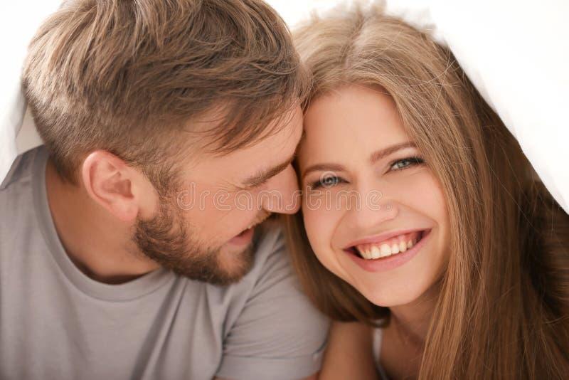 Pares novos felizes junto sob a cobertura na cama em casa imagens de stock royalty free