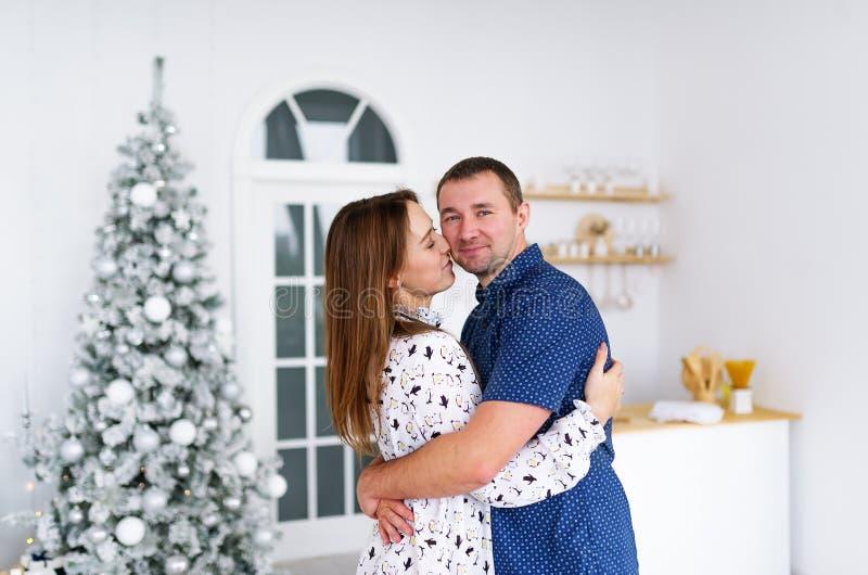 Pares novos felizes na decoração do Natal em casa Véspera de ano novo, árvore de abeto decorada fotos de stock royalty free