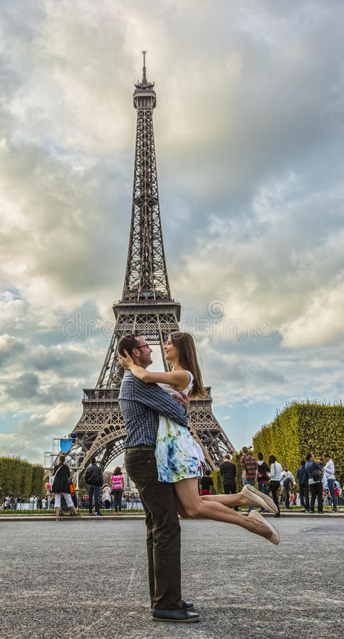 Pares novos felizes na frente da torre Eiffel foto de stock