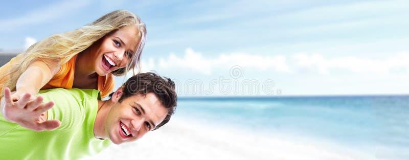Pares novos felizes na praia. imagens de stock