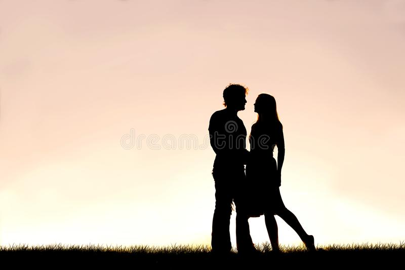 Pares novos felizes no amor mostrados em silhueta contra o por do sol no céu imagens de stock