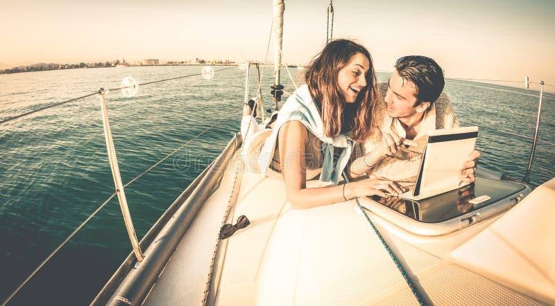 Pares novos felizes no amor no barco de vela que tem o divertimento com tabuleta imagem de stock royalty free