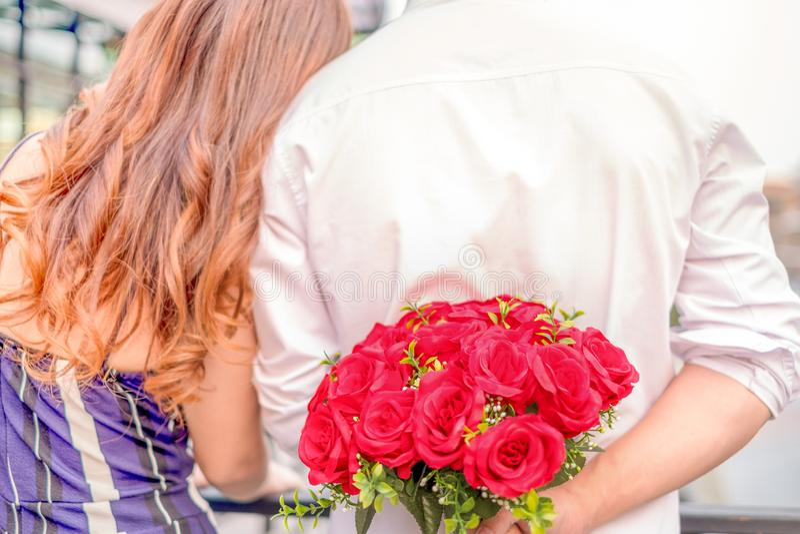 Pares novos felizes no amor que abraça e que guarda rosas vermelhas nas mãos para a surpresa sua amiga, conceito dos pares, a Din imagens de stock royalty free