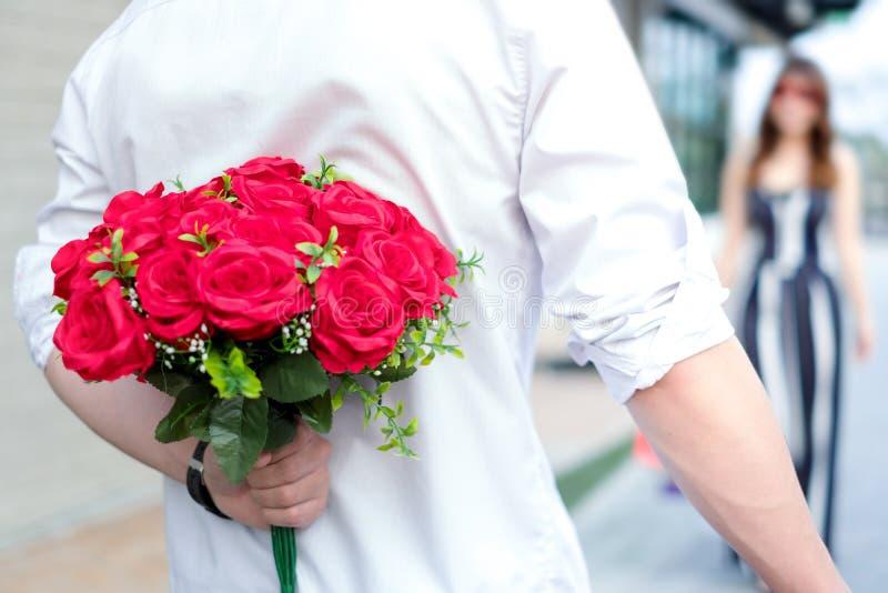 Pares novos felizes no amor que abraça e que guarda rosas vermelhas nas mãos para a surpresa sua amiga, conceito dos pares, a Din imagem de stock