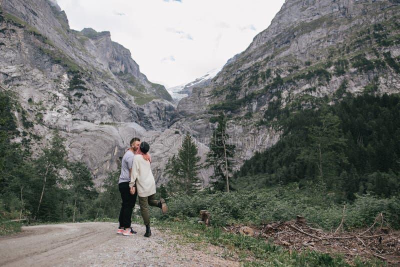 pares novos felizes no amor que beija ao andar fotografia de stock