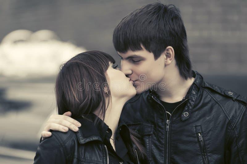 Pares novos felizes no beijo do amor exterior foto de stock