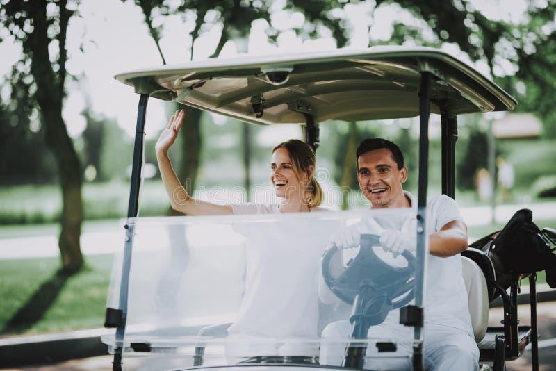 Pares novos felizes no carro branco no campo do golfe imagens de stock