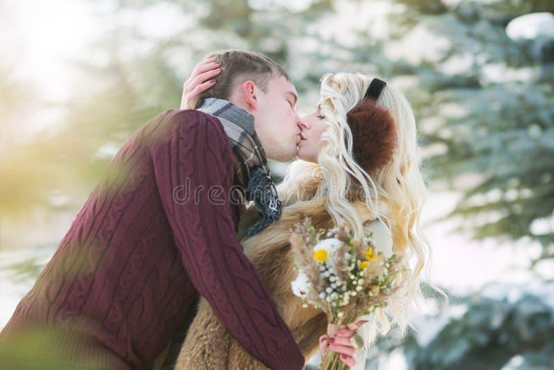 Pares novos felizes no parque do inverno no dia de Valentim fotos de stock royalty free