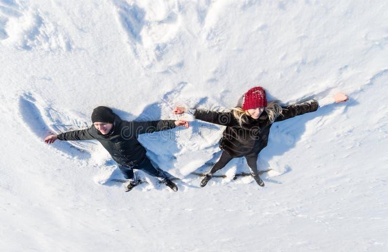 Pares novos felizes no parque do inverno que encontra-se na neve Vista superior fotografia de stock