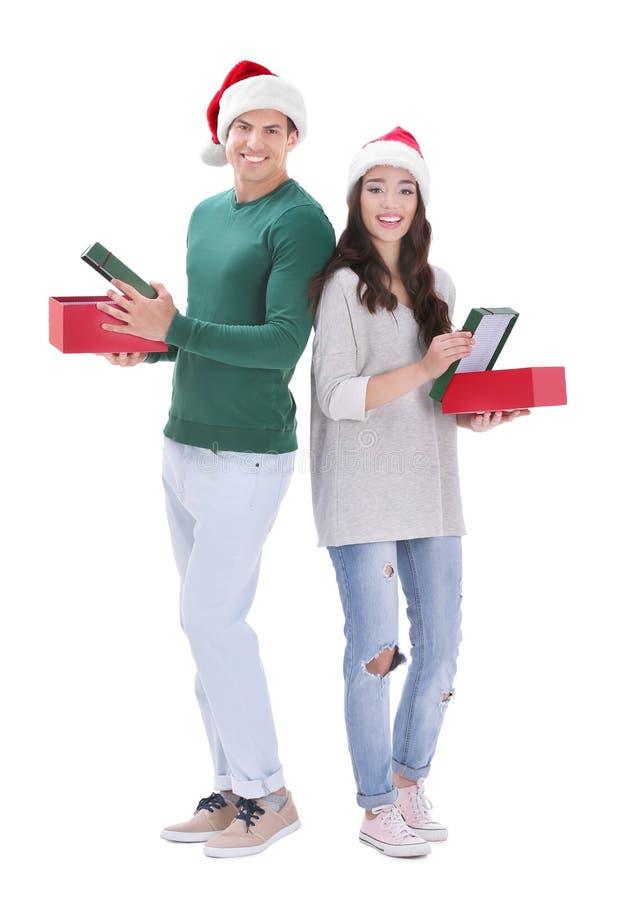 Pares novos felizes nos chapéus do Natal que guardam caixas de presente foto de stock