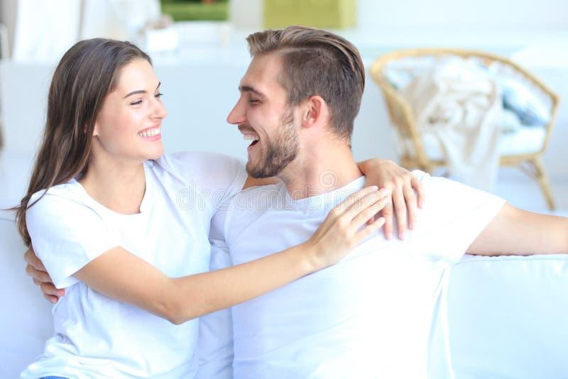 Pares novos felizes que abraçam e que olham se em casa interior fotografia de stock royalty free
