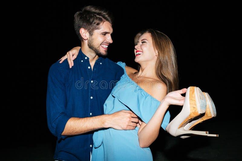 Pares novos felizes que abraçam e que riem da noite fotografia de stock