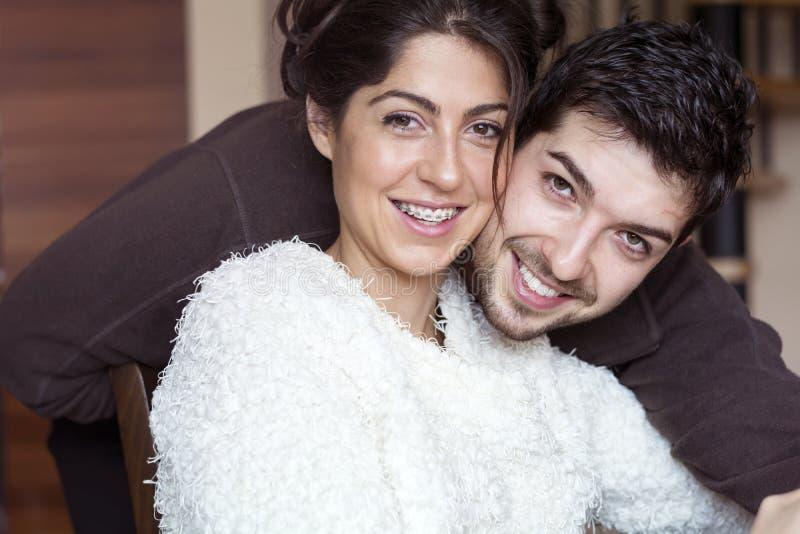 Pares novos felizes que abraçam e que sorriem internos fotografia de stock royalty free