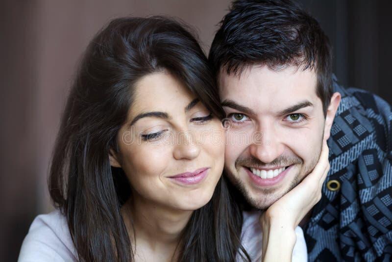 Pares novos felizes que abraçam e que sorriem internos fotos de stock royalty free