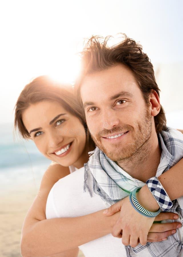 Pares novos felizes que abraçam na praia do verão imagens de stock