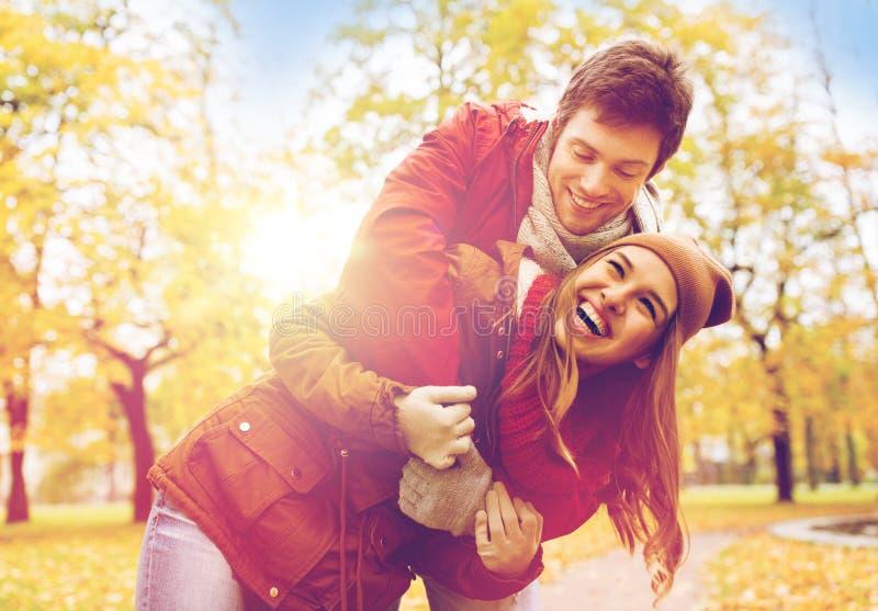 Pares novos felizes que abraçam no parque do outono foto de stock royalty free