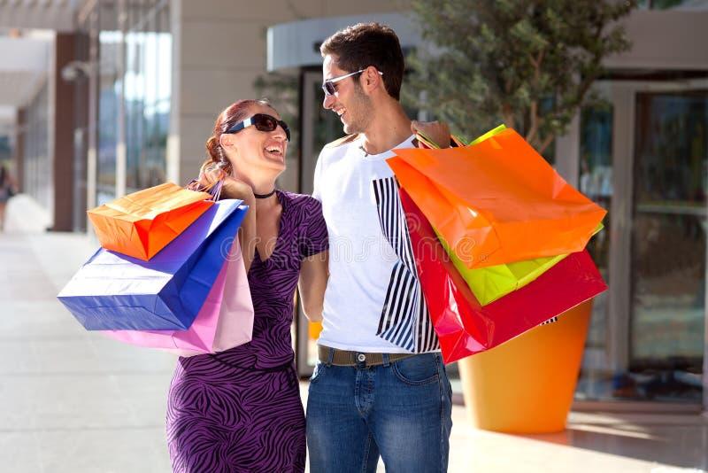 Compra nova feliz dos pares, sacos de compras coloridos levando. imagem de stock royalty free