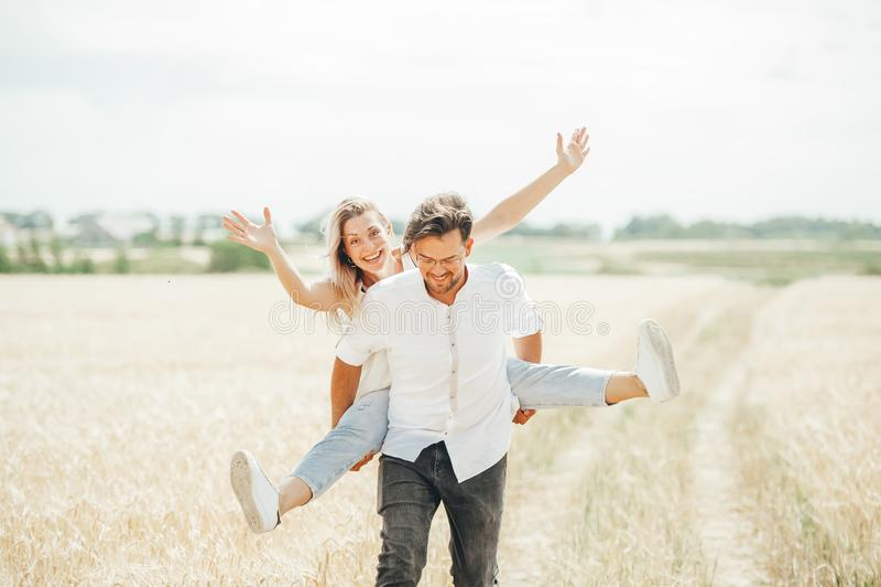 Pares novos felizes que apreciam no campo de trigo imagens de stock