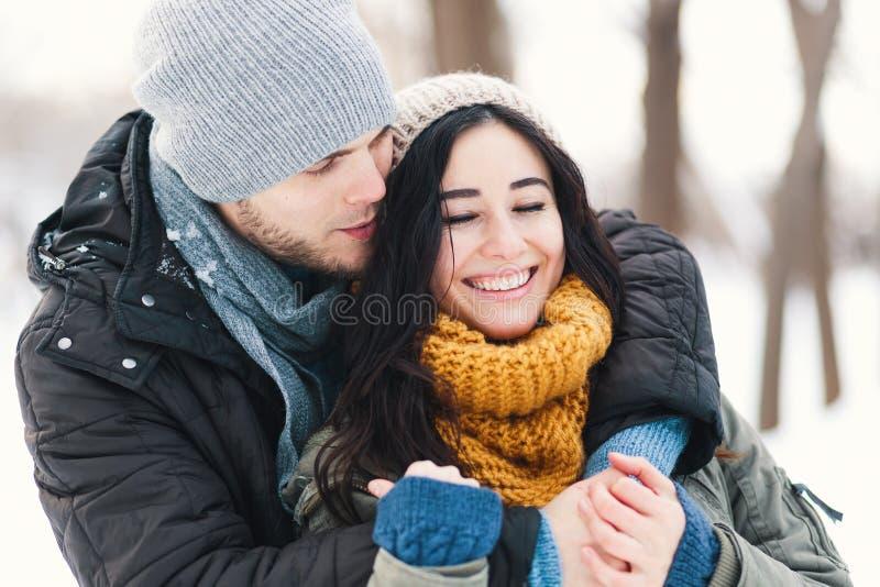 Pares novos felizes que apreciam os feriados de inverno que sorriem e que abraçam fotografia de stock royalty free