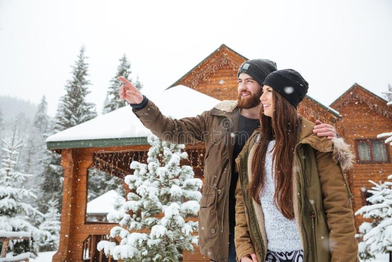 Pares novos felizes que apreciam a vista de montanhas do inverno fotografia de stock royalty free