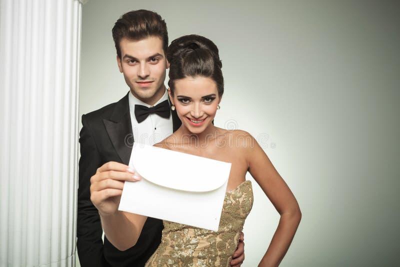 Pares novos felizes que apresentam um convite a seu casamento imagens de stock