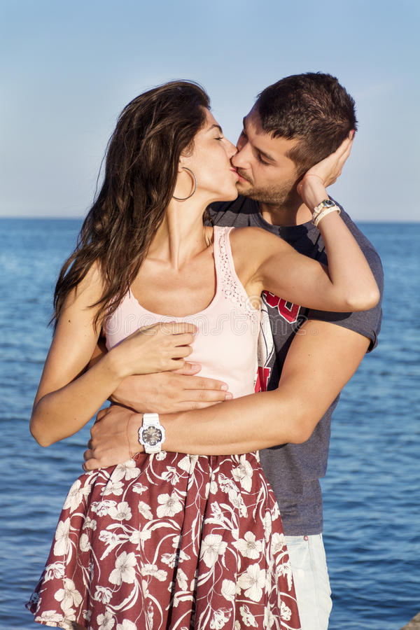 Pares novos felizes que beijam com amor em uma praia do mar foto de stock