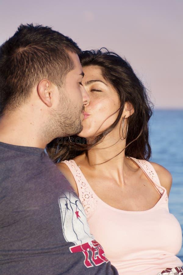 Pares novos felizes que beijam com amor em uma praia do mar fotos de stock royalty free