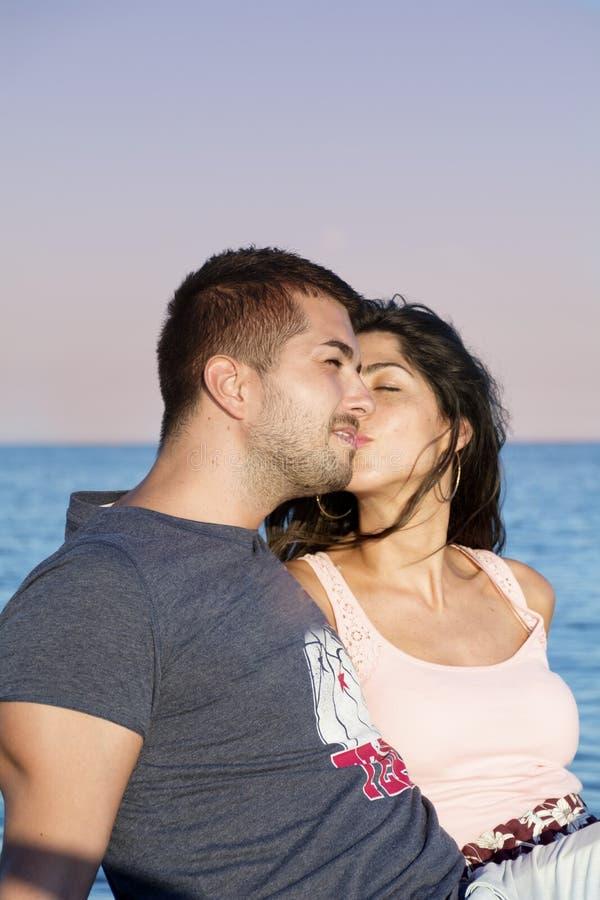 Pares novos felizes que beijam com amor em uma praia do mar imagem de stock royalty free