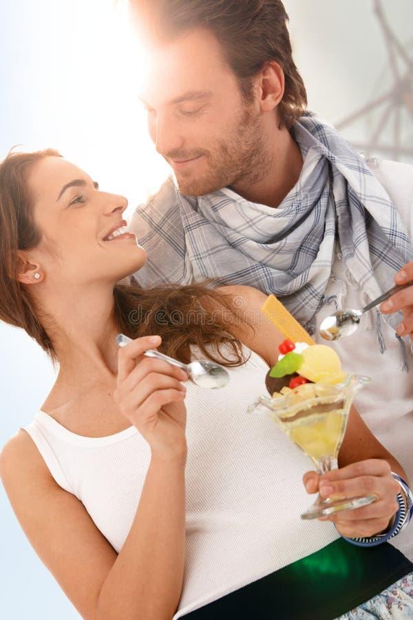 Pares novos felizes que comem o gelado no verão fotos de stock