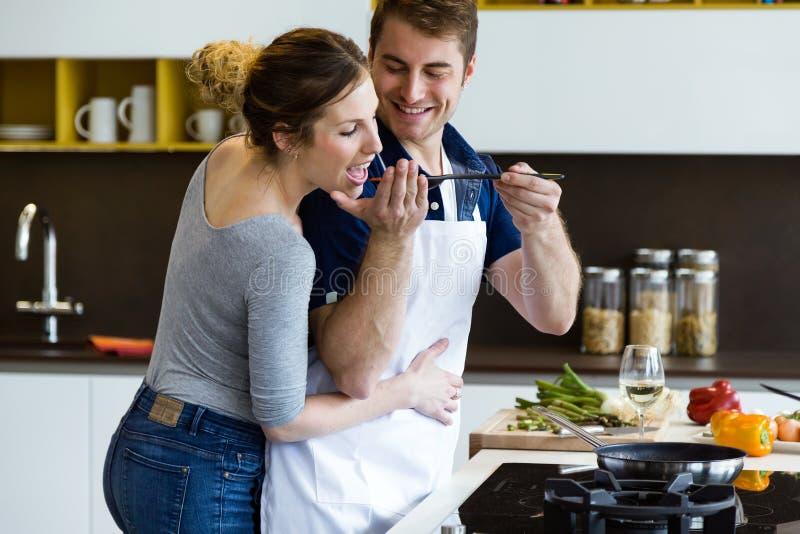 Pares novos felizes que cozinham junto na cozinha em casa fotos de stock royalty free