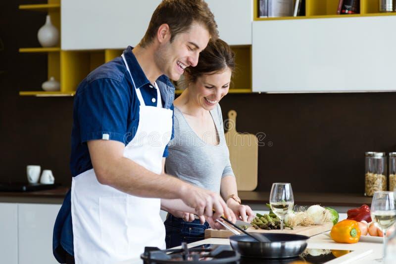Pares novos felizes que cozinham junto na cozinha em casa fotografia de stock royalty free