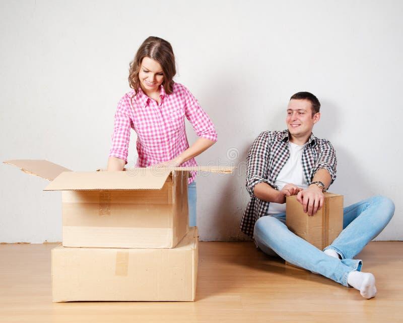 Pares novos felizes que desembalam ou caixas de embalagem e que movem-se em uma casa nova fotos de stock