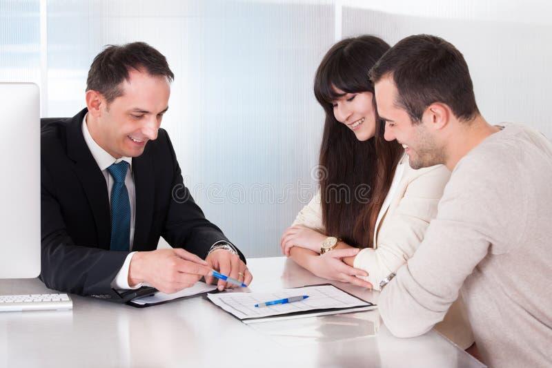 Pares novos felizes que discutem com o consultante fotografia de stock royalty free