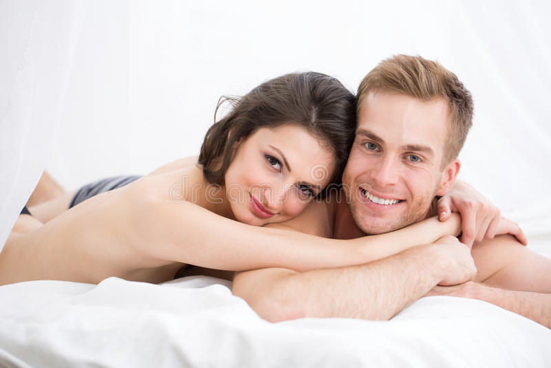 Pares novos felizes que encontram-se na cama branca fotos de stock