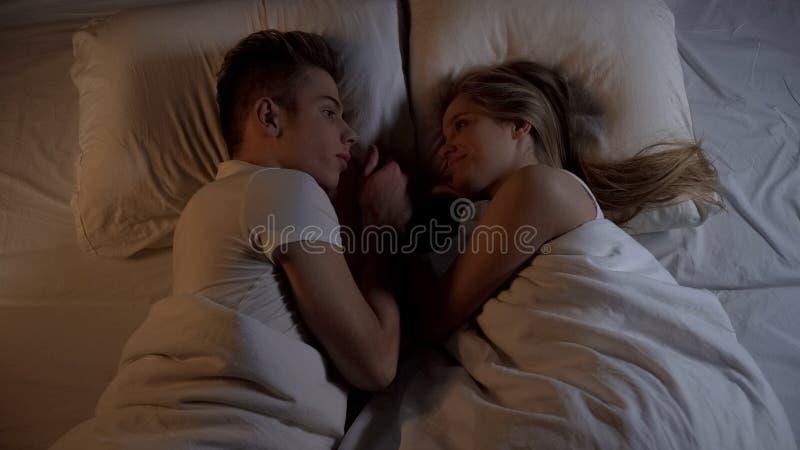 Pares novos felizes que encontram-se na cama na noite e que guardam as mãos, relações fortes foto de stock