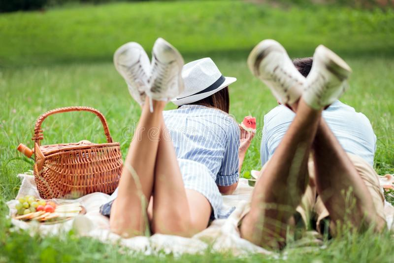 Pares novos felizes que encontram-se próximos um do outro e que comem as melancias, piquenique em um parque Vista de atrás fotografia de stock royalty free