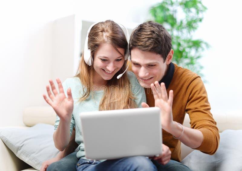 Pares novos felizes que falam através do computador com bate-papo video fotos de stock royalty free