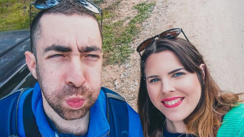Pares novos felizes que fazem as caras parvas e engraçadas ao tomar a imagem do selfie com seu smartphone ou a câmera no parque foto de stock