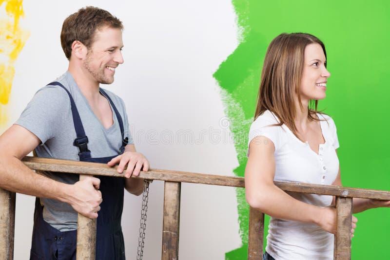 Pares novos felizes que fazem em casa redecorar imagens de stock royalty free