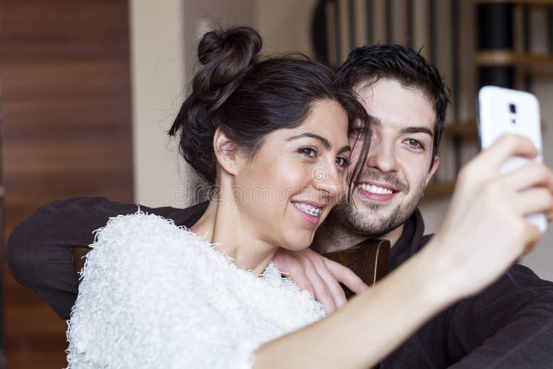 Pares novos felizes que fazem o selfie interno foto de stock